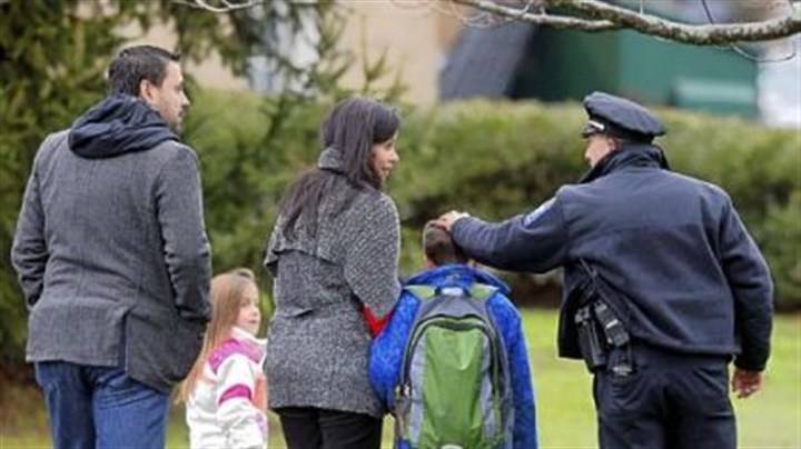 Easton, Conn., Easton, Conn., police officer J. Sollazzo greets a returning student Tuesday as he is walked into Hawley School in Newtown.