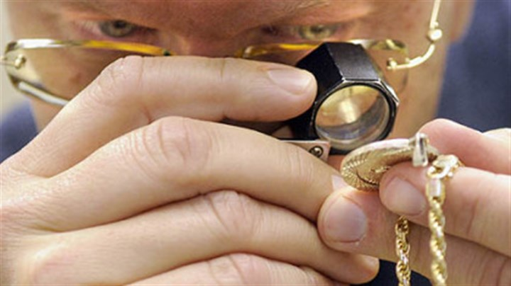 Eddie Lowy Eddie Lowy examines a piece of jewelry in his store, Banner Coin Exchange.