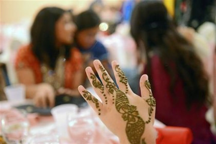 "eid henna A woman holds up her henna-painted hand to dry during Chaand Raat, ""moon night,"" a women-only celebration held the evening before Eid, with a feast, dancing and henna painting at the India Garden Banquet Hall in Monroeville on Thursday."