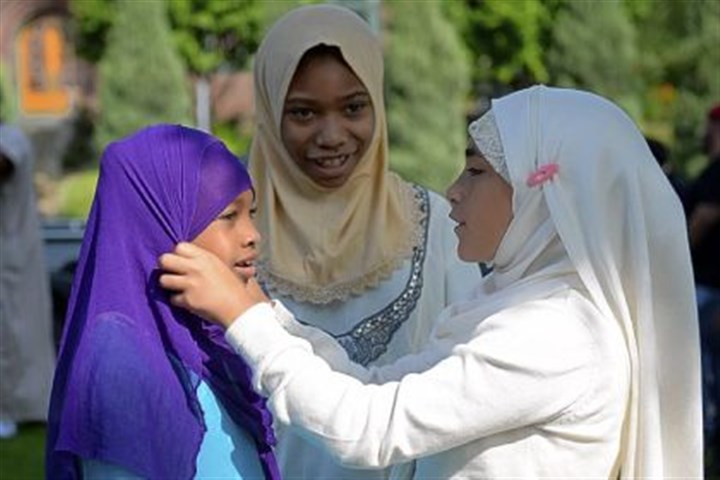 eid scarves Hajara Abdullah, 8, of Turtle Creek, left, gets some help with her head scarf from her cousin Malyla Perez, 11, of the North Side while her sister, Bilquisu Abdullah, 9, watches. On Thursday, they were at the Islamic Center of Pittsburgh during the celebration of Eid.