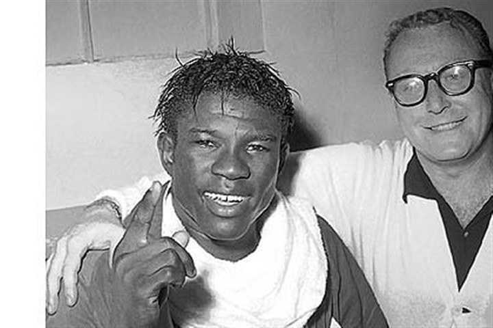 Emile Griffith 2 In this June 8, 1963, file photo, Emile Griffith smiles in the dressing room after regaining his welterweight world championship title by defeating Luis Rodriguez, at New York's Madison Square Garden. At right is Griffith's coach Gil Clancy.