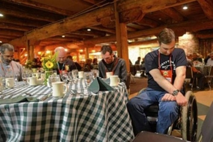 Erik Burmeister Erik Burmeister, right, a former Army National Guard member from Williamsport, Pa., bows his head for a prayer during a Wounded Warriors retreat banquet dinner held at Seven Springs Mountain Resort.