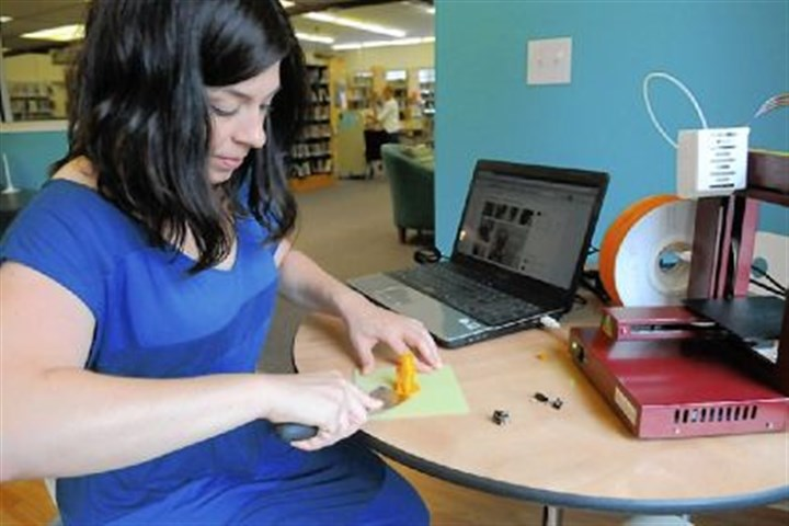 Erin Wincek Erin Wincek, library director of the Saxonburg Area Library in Saxonburg, removes a plastic owl she printed with the library's 3-D printer from its plastic base.