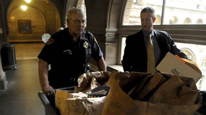Evidence Pittsburgh police Officer Terry Traxler, left, and Deputy District Attorney Mark V. Tranquilli take Poplawski trial evidence into the Allegheny County Courthouse before the start of Thursday morning's session.