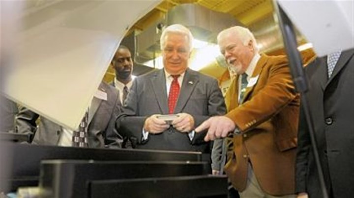 ExOne Kent Rockwell, right, chairman and CEO of ExOne, shows Gov. Tom Corbett parts manufactured by ExOne in North Huntingdon.