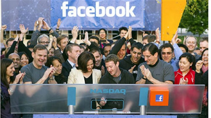 Facebook Mark Zuckerberg, chief executive officer of Facebook Inc., center, Sheryl Sandberg, chief operating officer of Facebook, center left, and Robert Greifeld, chief executive officer of Nasdaq OMX Group Inc., center right, remotely ring the opening bell for trading at the Nasdaq MarketSite from the Facebook campus in Menlo Park, California, U.S., on Friday.