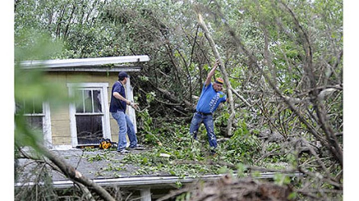 Fallen trees Barry Hines, left, of Mihalko General Construction and Denny Bloom of Johnstown work Saturday on clearing fallen trees from the home of Dorothy Felbaum along Route 711 in Ligonier after an EF1 tornado swept through the area Friday.