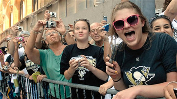 Fans Fans cheer the Penguins as they parade along Grant Street.