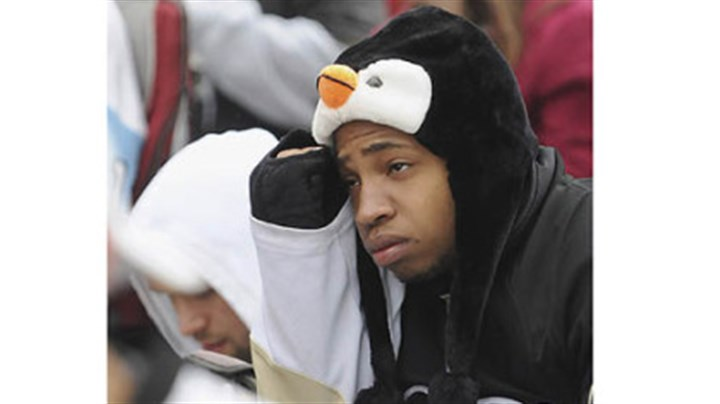 Fans frown University of Pittsburgh student Manny Moorer of Charlotte, N.C. frowns at the Penguins' declining fortunes as fans gathered in the cold outside the Consol Energy Center to watch Game 6.