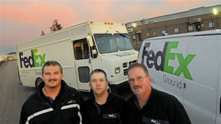 FedEx workers Bill Floyd, Tom Dunlap and Paul Bullock in front of their delivery trucks and the Neville Island FedEx warehouse.