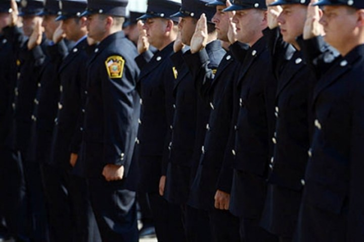 fire graduates in dress blues The firefighting recruits take an oath of service during their graduation ceremony.