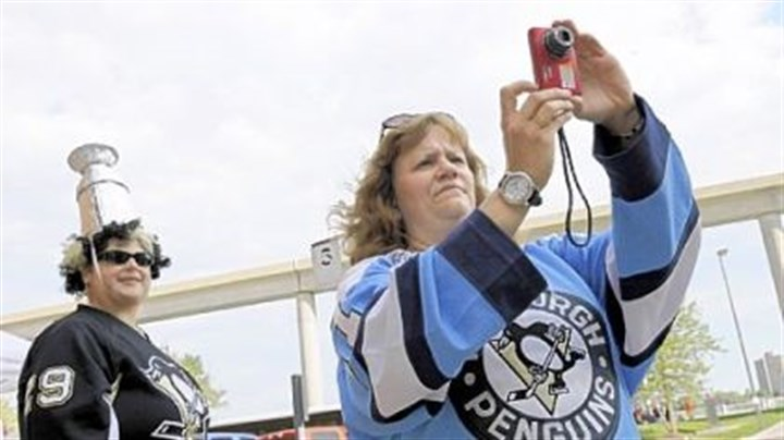 First shot Elaine Anderson, of Ross Township, takes a photo of the Penguins' team bus arriving at Joe Louis Arena in Detroit yesterday. At left is her friend, Christine Szymarek, of White Oak.