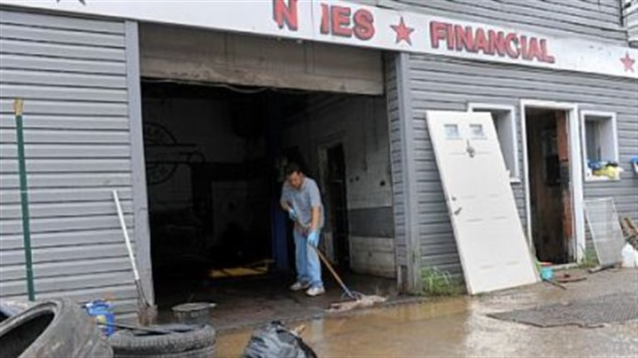 flood Rick Ibrahim sweeps out water from Best Auto Mart along Route 51 in the South Hills on Saturday after strong storms caused flash flooding Friday evening.