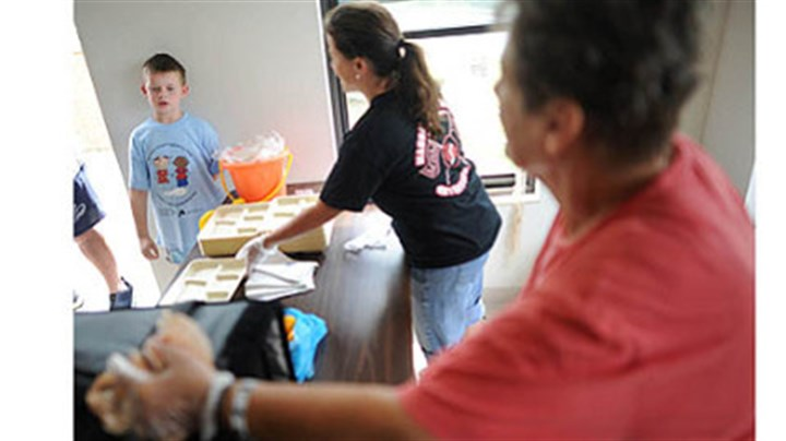 Food service program Cafeteria cooks Mary Bish, center, and Barb Rush, right, prepare to serve Robin Tracy, 9, as he walks up to the counter as the Central Greene School District's Summer Food Service Program makes its daily stop at the Valley Farm Drive apartments in Waynesburg.