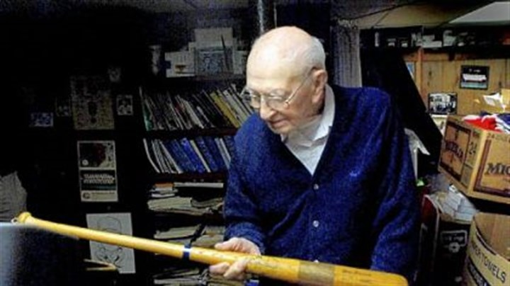 Former scout Elmer Gray, 86, who served as a scout for the Pittsburgh Pirates and the Cincinnati Reds during a long career in baseball, examines a commemorative bat from the 1970s.