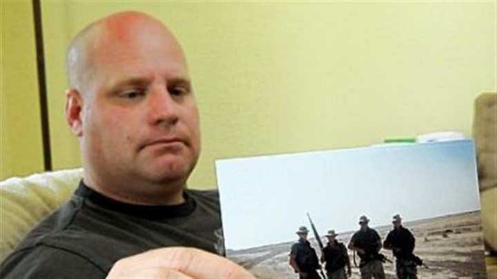 Former West Virginia National Guardsman Former West Virginia National Guardsman Russell Powell holds a photo of him on patrol near a water treatment plant in Basrah, Iraq, in 2003. where he was likely exposed to hexavalent chromium, a toxic chemical.