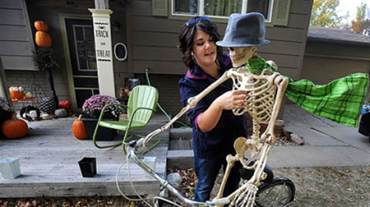 Front yard decor Paige Kaske threads a wire through the ribcage of a skeleton to create the effect of a scarf blowing while decorating her yard this week for Halloween in Sioux Falls, S.D.