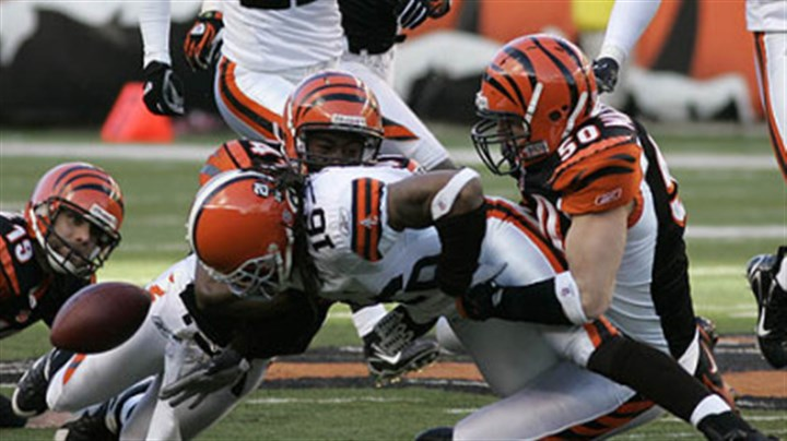 Fumbled football Cleveland Browns kick-returner Joshua Cribbs (16) fumbles the ball as he is tackled by Cincinnati Bengals defenders Chinedum Ndukwe (41) and Jim Maxwell (50) in the second half of yesterday's game in Cincinnati. Kyle Larson (19) watches. Cleveland recovered the fumble, but lost the game, 19-14.