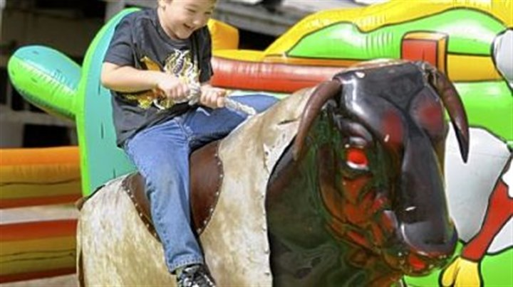 Garett Kime Garett Kime, 6, of Clarksville tries to hold on as he rides the mechanical bull Sunday at the 2012 Roughneck Fest at the Washington County Fairgrounds.