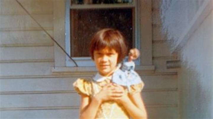 Girl with Barbie An old photo of Kim Fancsali holding her first Barbie doll on her back porch when she was about 5 years old.