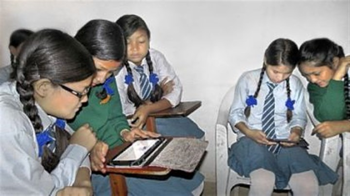 Girls explore e-readers Girls sponsored by the Rukmini Foundation explore e-readers donated for their use.