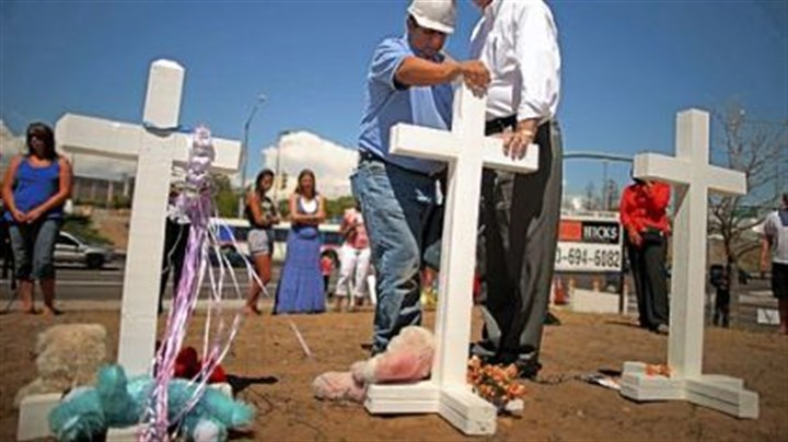 Greg Zanis Mayor Steve Hogan Greg Zanis, left, a carpenter from Aurora, Ill., prays with Aurora, Colo., Mayor Steve Hogan at the 12 crosses Mr. Zanis made for a makeshift memorial to the victims of the weekend's mass shooting in suburban Denver.