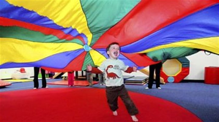 Gym dandy Jack Viti, 3, revels beneath a billowing parachure at the River Kids Gym in Indiana Township. The gym also is equipped and staffed to serve children with special needs, enabling them to play along with other children.