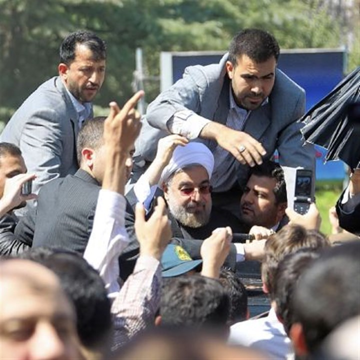 Hasan Rouhani surrounded Iranian president Hasan Rouhani is surrounded by bodyguards Saturday after a shoe was thrown at his car while his motorcade was leaving Tehran's Mehrabad Airport after he arrived from New York.