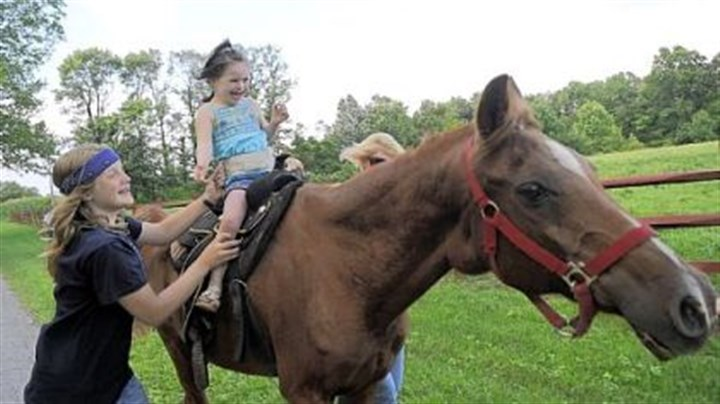 "Healing power of horses Emily Lane, 5, of Mars, giggles as she trots on ""Taco"" with help from Stehanie Schaefer of Grove City at the Hidden Hope Ranch in Grove City."