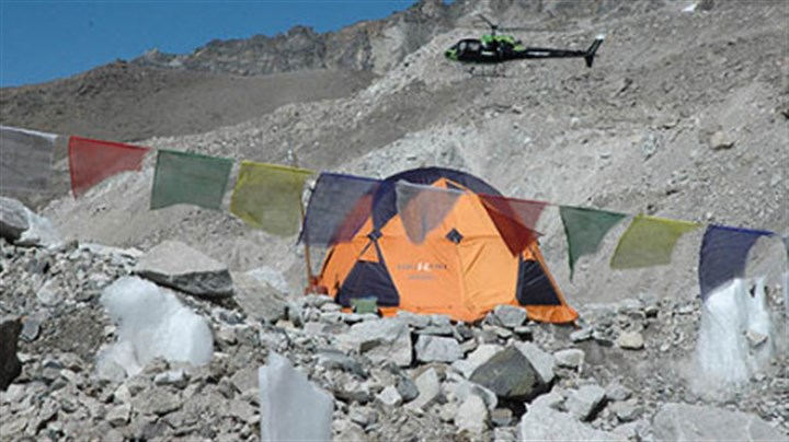 Helicopter lands at base camp A rescue helicopter lands just outside the author's tent the morning after an avalanche killed one Sherpa and critically injured two climbers. Helicopter evacuations from Everest Base Camp are only possible in the morning because cloud coverage later in the day pose great danger to flights.