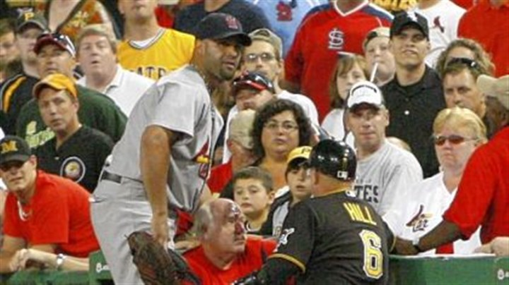 Hit and done Pirates first base coach Perry Hill and Cardinals first baseman Albert Pujols attend to a fan down the first base line struck by a Garrett Jones foul ball in the seventh inning Friday night. Paramedics took the fan from the field.