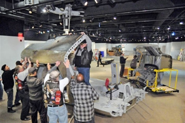 "Huey Heinz History Center Vietnam War veterans help assemble a UH-1H ""Huey"" helicopter at the Heinz History Center to be displayed in the upcoming exhibit, ""1968: The Year That Rocked America."" The exhibit's helicopter, which flew with the Army in Vietnam from 1967 through 1970, is the largest artifact ever at the museum."