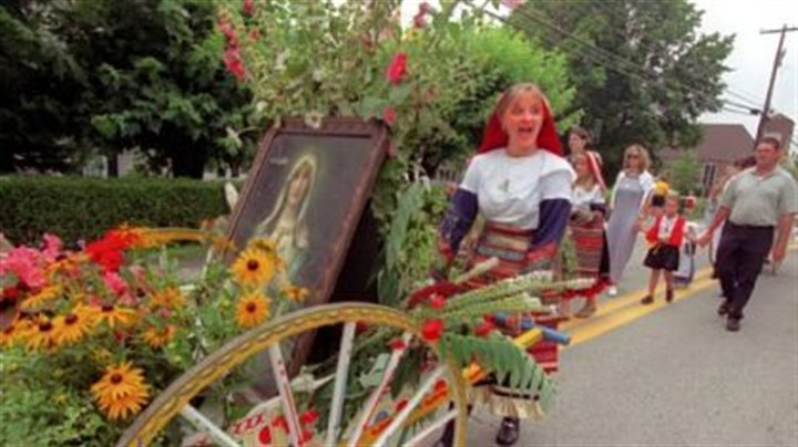 In 2000 In 2000: Ashley Kessler responds to spectator cheering as she pushes a cart filled with flowers and a portrait of Our Lady of Mount Carmel as she and other parishioners march in the parade after Mass at St. Bartholomew Catholic Church, Crabtree, down the street and back.