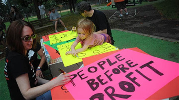 In Lawrenceville Keira Lee Gibson, 3, of Lawrenceville, watches as Maureen Sandefer of Boulder, Colorado creates a sign as people start to gather in Arsenal Park in Lawrenceville for an unpermitted march to Downtown.