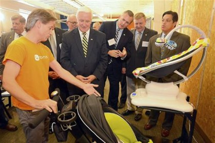 Innovate in PA Henry Thorne, left, of 4moms shows Gov. Tom Corbett his company's infant products, including a stroller that unfolds and collapses at the push of a button and a playpen that opens and closes at the push of a button, during his visit to Innovation Works' Alpha Labs on the South Side to announce a new program, Innovate in PA.
