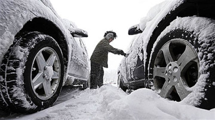 Iowa snow Noah Nichols of Des Moines, Iowa, cleans snow from his car early Thursday. The first widespread snowstorm of the season began a slow crawl across the Midwest with some areas receiving as much as 15 inches.