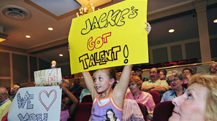 "Jackie Evancho fans Kathrine Kelly, 8, holds up her sign at the Kean Theater at St. Barnabas in Gibsonia where well wishers gathered to watch Jackie Evancho on ""America's Got Talent."""