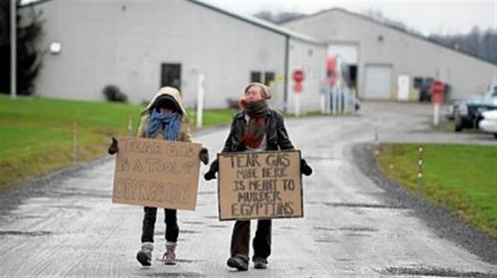 Jamestown About two dozen protestors - some carrying handmade signs, others symbolically wearing surgical masks or gas masks - gather Thursday at the Combined Systems Inc. plant in Jamestown, Mercer County, to protest the manufacturing and selling of tear gas to Egypt.