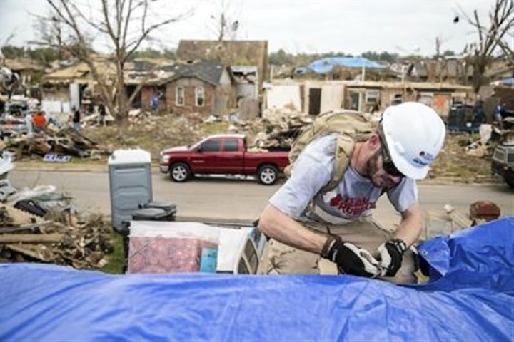 Kirk Jackson/Team Rubicon Army veteran Andy McIntoch works to secure a tarp on a damaged roof after a tornado hit and before the coming rains in Moore, Okla., three weeks ago.
