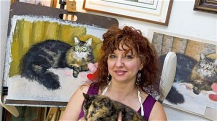 "Kitty calendar Bernadette Kazmarski, an animal portrait artist who created ""Great Rescues,"" a calendar that features portraits of cats, in her home studio in Carnegie with her 19-year-old cat, Cookie."
