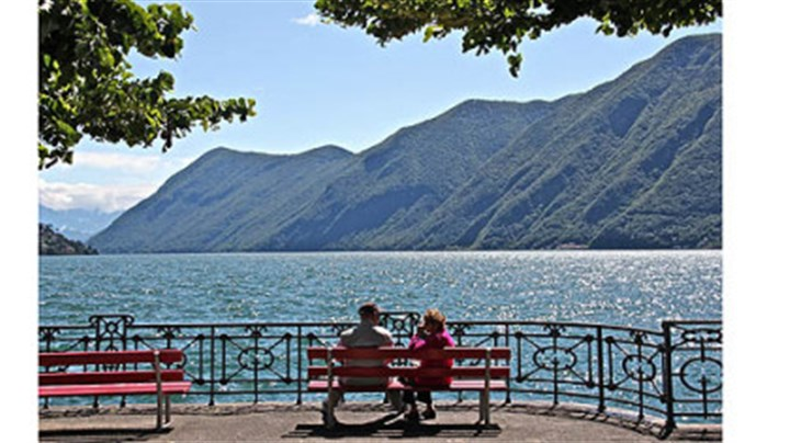 Lago Lugano A couple takes in the view from the promenade, Lago Lugano, Switzerland.