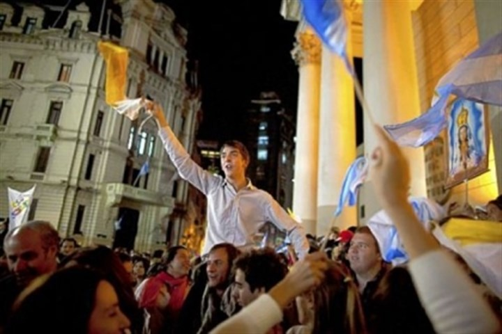 Latin Americans Faithful wave Vatican and Argentinian flags Wednesday as they sing outside the Metropolitan Cathedral in Buenos Aires, Argentina. Latin Americans reacted with joy on Wednesday at news that Argentine Cardinal Jorge Mario Bergoglio was elected pope. Cardinal Bergoglio, who chose the name Pope Francis, is the first pope from the Americas.