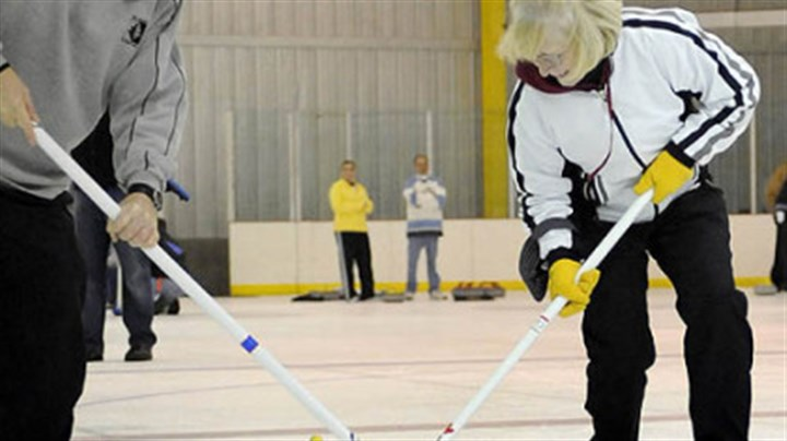 "Learn to curl Ron Katila and Ann Byrd, both of Mt. Lebanon, brush the stone during a ""learn to curl"" class at the Robert Morris University Island Sports Center on Neville Island."