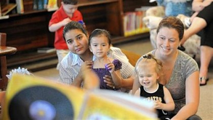 Library Awantika Kumar, left, of Carnegie, her 2-year-old daughter, Aarna, 15-month-old Elizabeth Glance and her nanny, Jennifer Matta, 28, attend a story-telling session at the Andrew Carnegie Library.