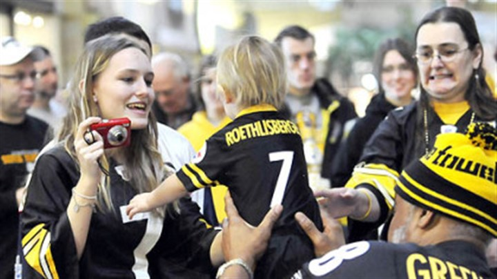 Little Steeler Man Brittany Jenkins, of Cabot, reaches for her son, Caleb, as former Steeler L.C. Greenwood passes him back after a photo yesterday during the Steelers tailgate party at The Galleria at Pittsburgh Mills in Frazer.