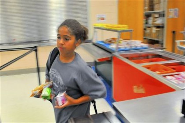 lunch 6 Devonn Kyles, 12, a seventh-grader at South Brook Middle School, grabs breakfast on the run.