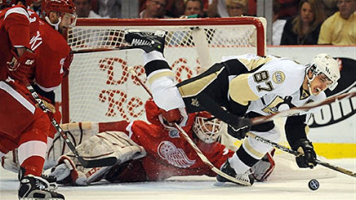 Making a save Detroit goalie Chris Osgood makes a save on Sidney Crosby in the first period last night.