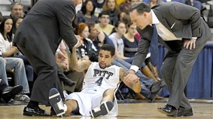 Man down Pitt athletic trainer Tony Salesi, left, and coach Jamie Dixon assist John Johnson after he was slow to get up against Cincinnati in the first half Sunday night at Petersen Events Center.
