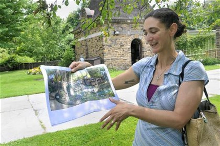 Marijke Hecht Marijke Hecht displays a rendering Thursday showing what a rebuilt Frick Environmental Center would look like. She is standing at the entrance to what remains of the old center, which was destroyed by a fire in 2002.