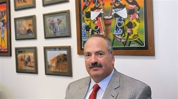 Michael Ginsberg Michael Ginsberg, a partner with Jones Day law firm, sits with photographs and paintings from Kenya. Mr. Ginsberg volunteered his time to train trial lawyers in Nairobi.